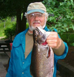 A fisherman holding a very large brook trout