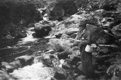 Black and white photo of a man in a fedora trout fishing in a rocky stream