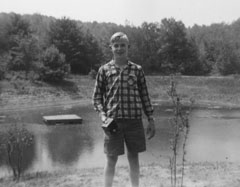 A black and white photo of a young man wearing shorts standing in front of a pond