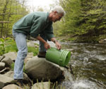 A man pours fish from a green bucket into a stream
