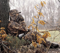 A turkey hunter in camouflage sits with his gun leaning against a tree