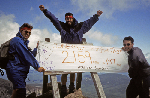 A man and his two friends who hold a banner, celebrate the end of his hike of the Appalachian Trail on a mountain top