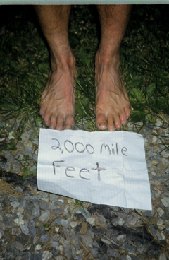 Two bare feet with a sign reading '2000 mile feet'