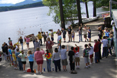 A group of campers standing in a circle by the lake