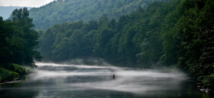 A solitary fly fisherman in the middle of a misty river surrounded by forested hills