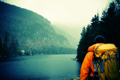A person in an orange jacket with a yellow backpack looks at a lake surrounded by steep, forested hills