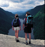 Two hikers high on a rocky ledge overlooking a lake and forest