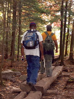 Two people with small backpacks hiking on a trail