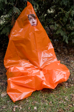 A woman sitting inside an orange contractor trash bag with a hole cut out for her face