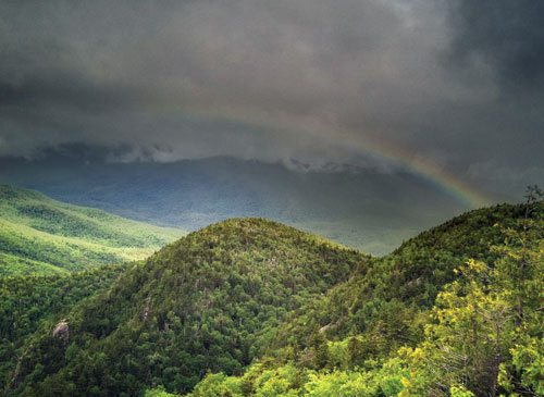 A rainbow arcs across a dark, cloudy sky over the green mountains