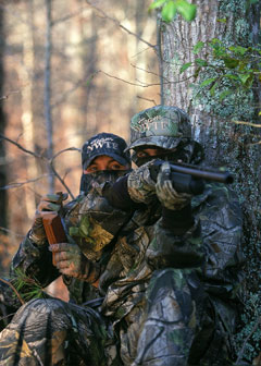 Two turkey hunters in full camoflage with guns at the base of a tree