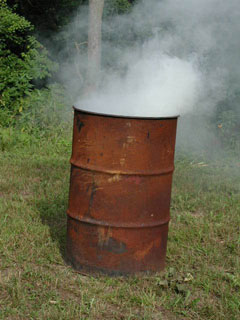 A smoking, rusted burn barrel