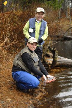 A woman and a young girl fishing. The woman holds a brook trout