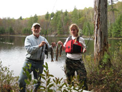 Two anglers pose at the edge of a pond with the brook trout that they caught
