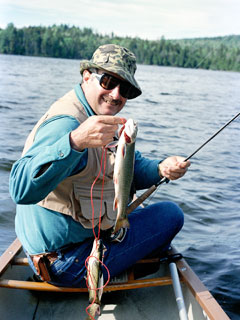 A man in a boat on a pond holding up a trout in one hand and his fishing rod in another
