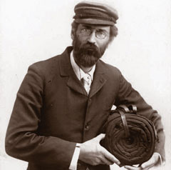 A photo of a man with a beard, glasses, cap and a rolled blanket under his arm.