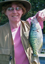 A woman in a pink shirt and tan vest holds up a fish