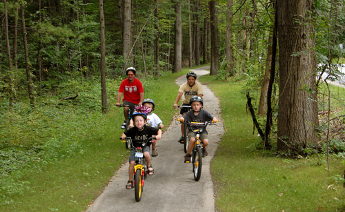 A family riding on a bike trail along the woods edge