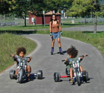 Two young children on tricycles with their mother on rollerblades behind them