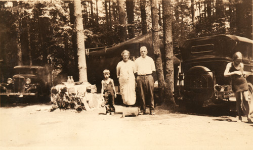 Old photo of three campers standing infront of their campsite