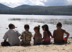 Five kids sitting at the waters' edge