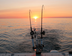 Two fishing poles with the sun setting beyond