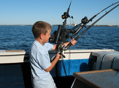 Young boy on a boat holding a fishing rod