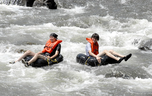 Two young men riding whitewater in tubes