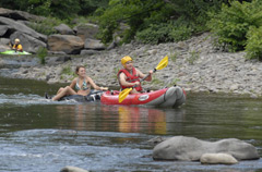 Kayaker paddling with a girl bhind him, tubing