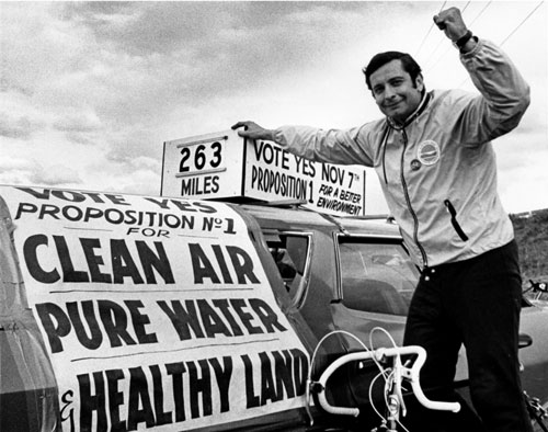 Former DEC commissioner Henry Diamond on a bicycle leaning against a can with political slogans