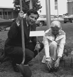 Former DEC Commissioner Henry Diamond and a woman planting a tree seedling