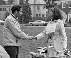 Former commissioner Diamond shakes hands with a woman holding a bike