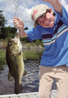 A smiling young boy with the largemouth bass he caught