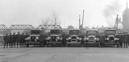 A 1926 black and white photo of a line of fire control vehicles and forest rangers
