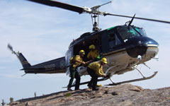 Forest rangers getting off a helicopter.