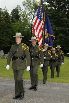 Rangers marching single file in uniform with two flags