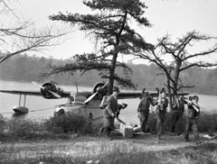A float plane docked at the shore of a lake with forest firefighters carrying equipment