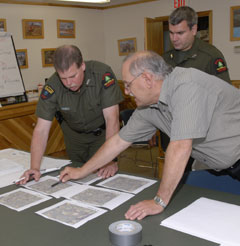 DEC Forest Rangers and another man look at reports on a table