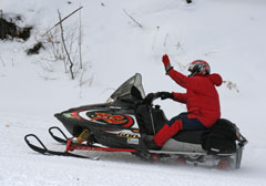 A snowmobiler in a red jacket riding