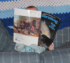 A baby on a couch holding a copy of Conservationist in front of her.