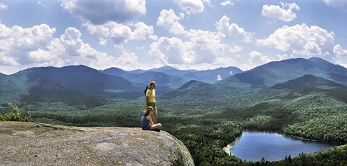 Two hikers enjoying the view of the Adirondacks from the rocky summit of one of the mountains