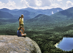 Two people admiring the view from the rocky summit of an Adirondack mountain