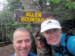 A man and woman stand by a tree with the Allen Mountain sign on it
