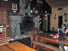 Interior photo of an Adirondack lodge with a large fireplace and dining table
