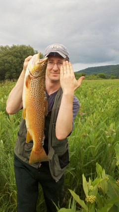 A man holds up a large brown trout with one hand, using his other forearm and hand for size comparison