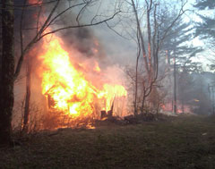 A house in the woods consumed in flames