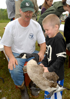 A young boy holds a Canada goose by the wings while a man in a green cap and white t-shirt looks on