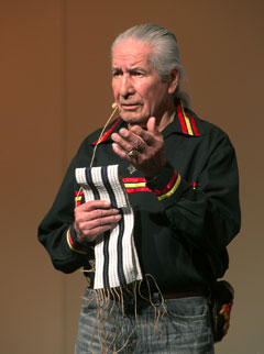 An elder Native American man holds the two-row wampum