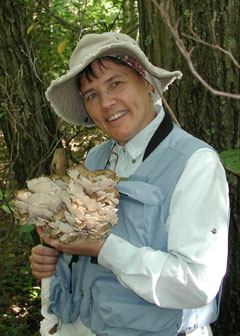 The author's wife holds a large group of hen of the woods mushrooms