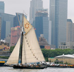 A sailboat on the river with New York City buildings behind